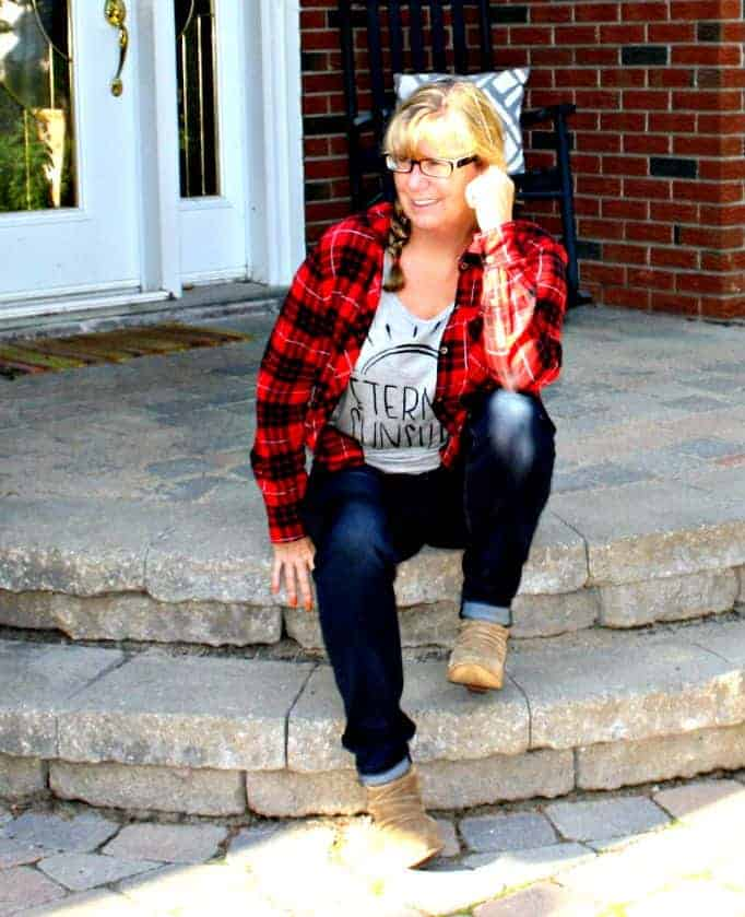 sitting in haggar dream jeans and a buffalo plaid shirt with rodeo boots