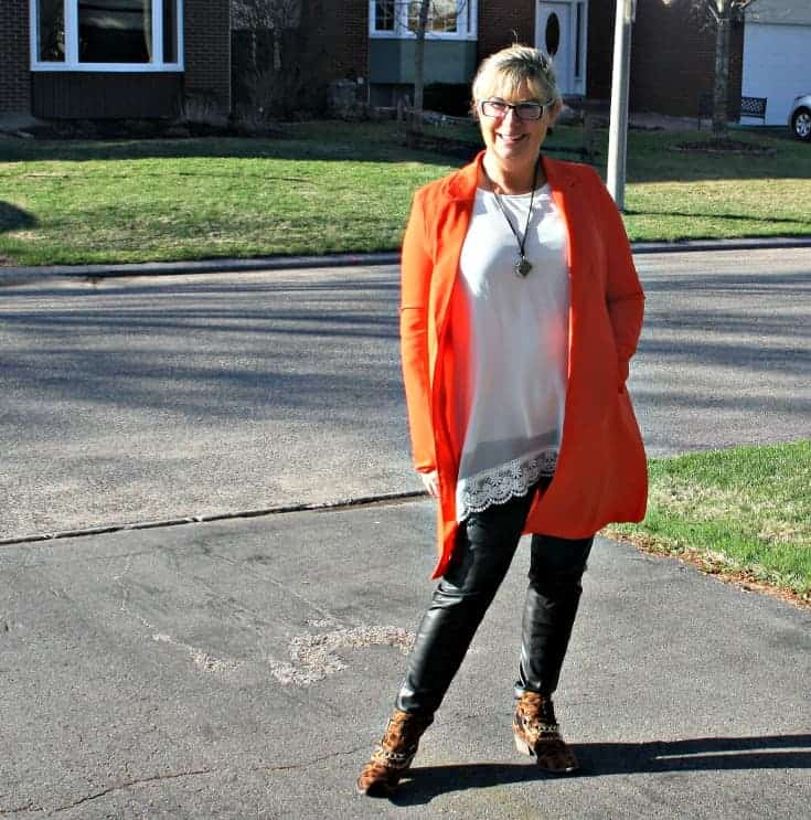 Cream tunic and leather leggings with a leopard boot, topped with an Orange Shein Blazer and a camera necklace from New Look