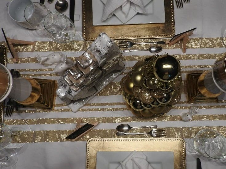 white and gold table settings with a gold charger and napkin rings