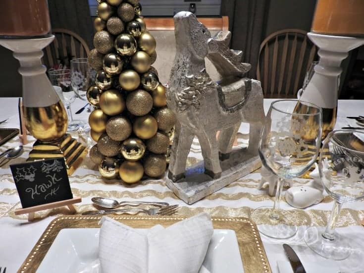 white and gold table settings with a gold tree and reindeer