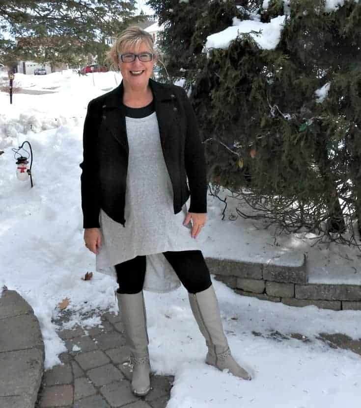 smiling in the snow in Heather grey tunic with a moto and shoe dazzle boots