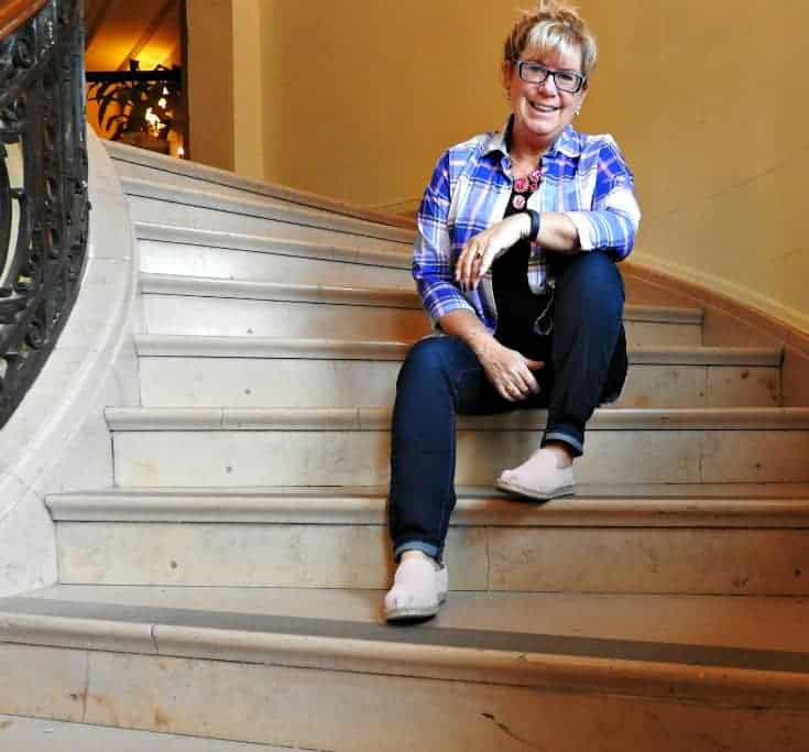 lounging on the stairs in Old Navy Plaid and Haggar Dream Jeans with a Flaunt it 7 Charming Sisters necklace at the Chateau Laurier