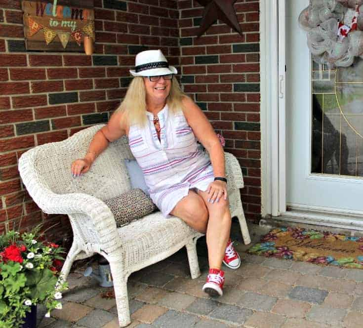 sitting on a white couch with Red converse and a striped dress from Old Navy with a fedora