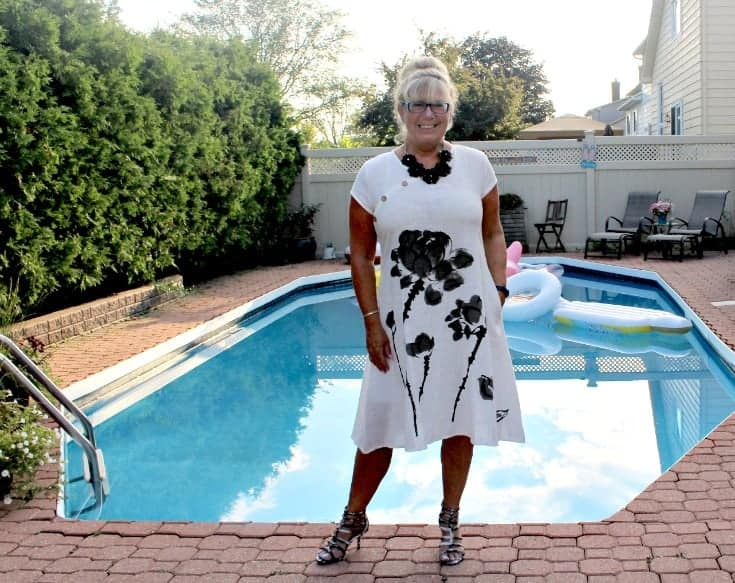 relaxing poolside in Fashion Mia White Linen Shift with a black floral necklace