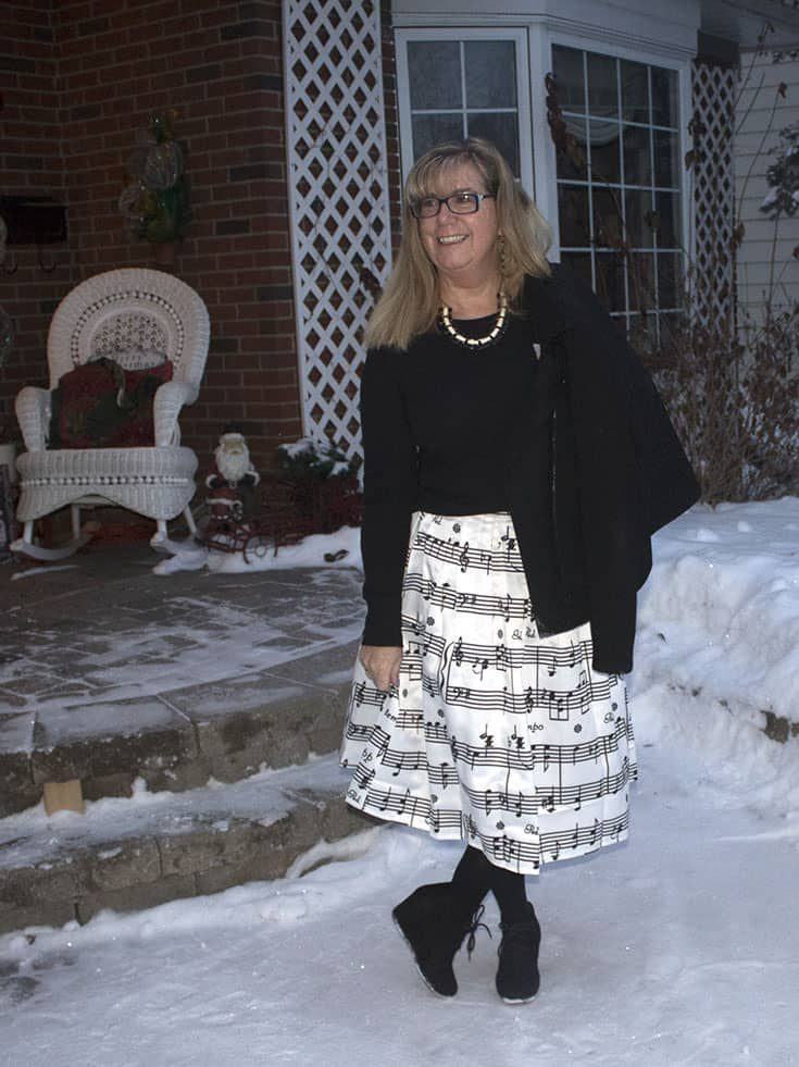 Music note skirt with a henley and a black wool moto jacket with black suede skecher wedges against the snowy background