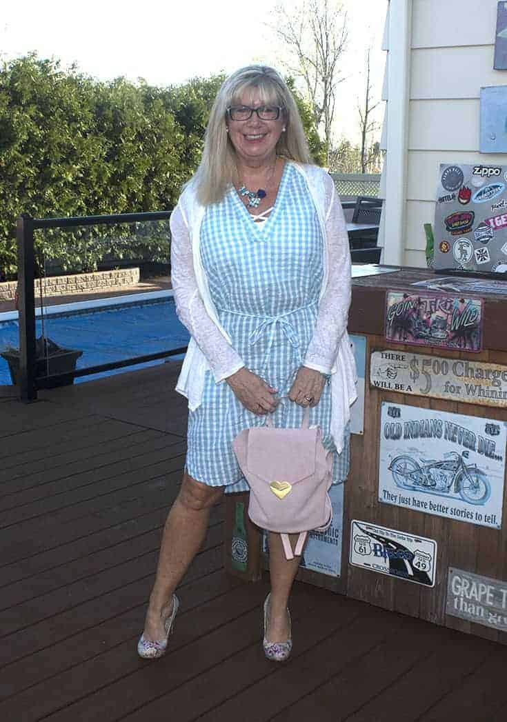 Blue gingham dress with pastel floral shoes and a white drape cardigan