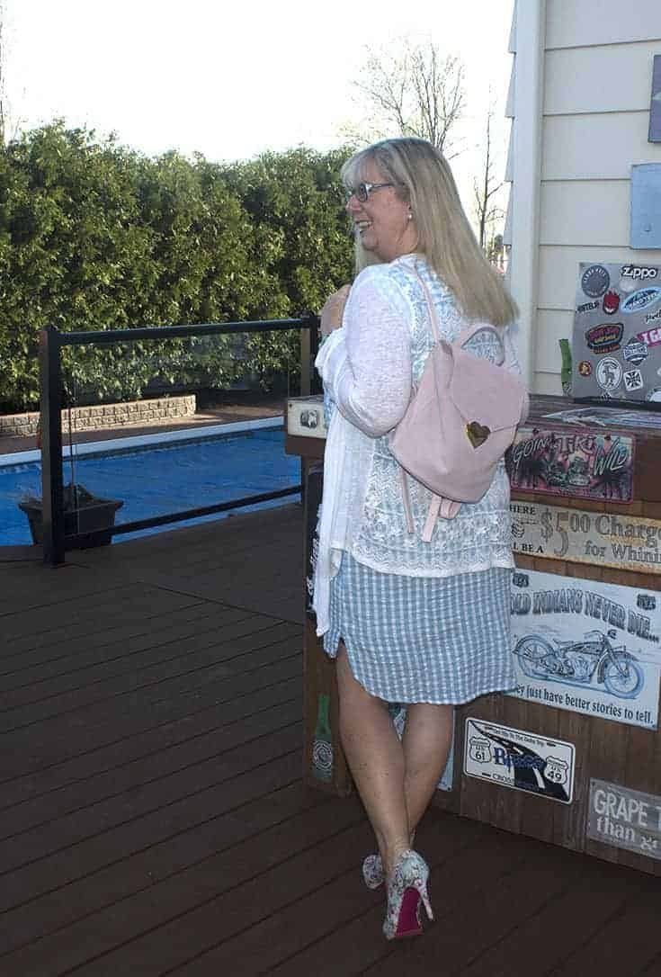 Blue gingham dress with pastel floral shoes and a drape cardigan with a Drew Knapsack
