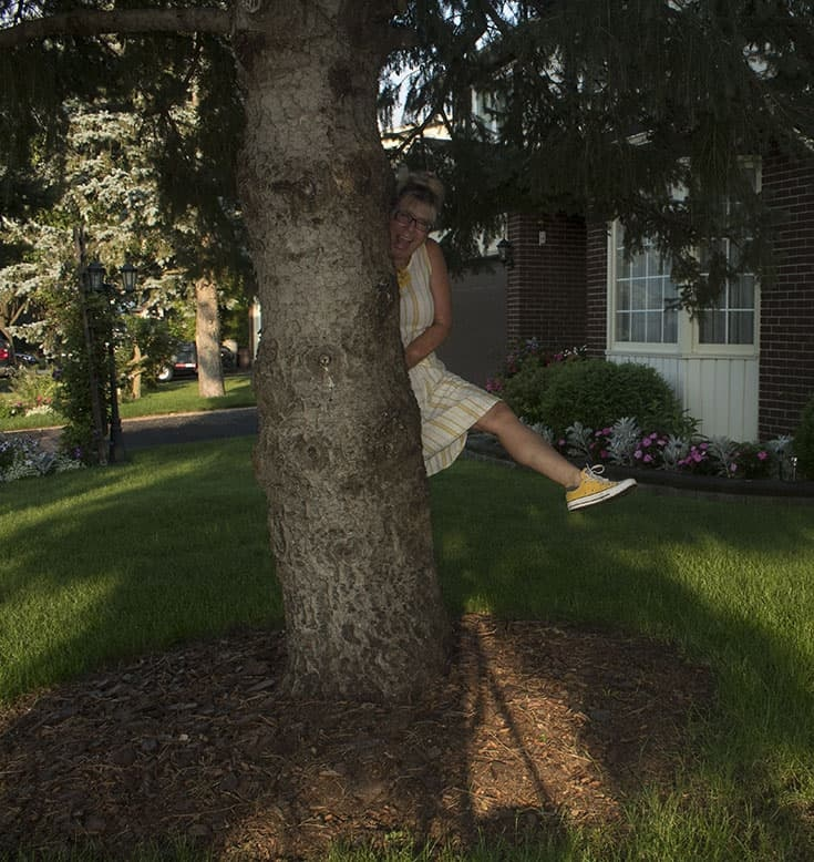behind a tree in linen shift from old navy and converse
