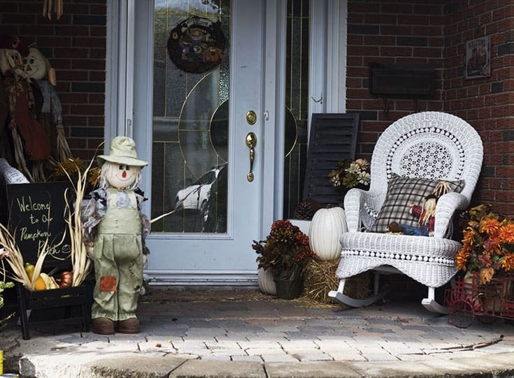 Fall porch decor with scarecrows and pumpkins and white wicker