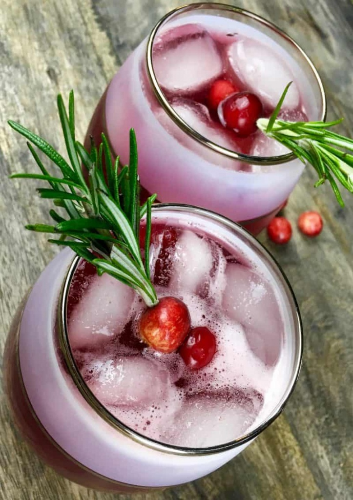 Cranberry Spritzer in a glass with rosemary garnish