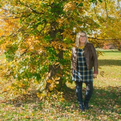 standing by a tree in fall colours in an Old Navy dress
