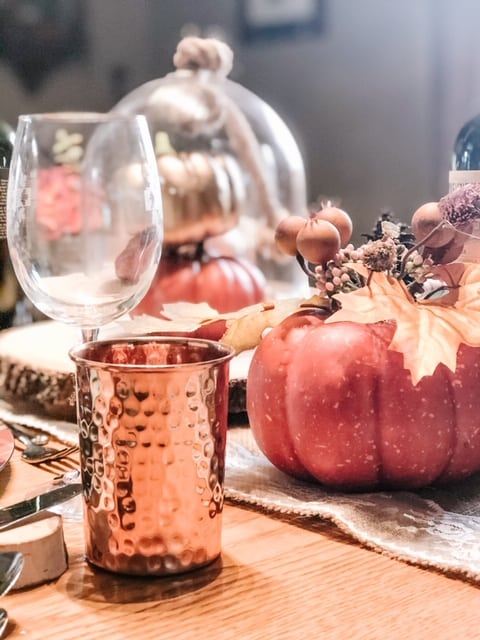 cooper mugs and pumpkins on a table