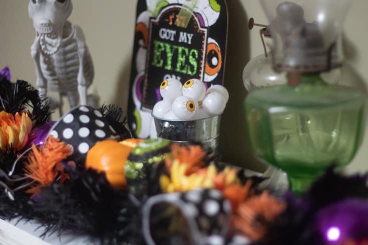 halloween sign and bucket of eyeballs on a mantle