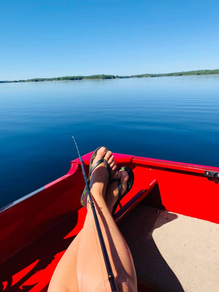 re boat and fishing pole on the lake