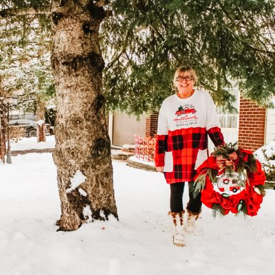 standing in the snow with a wreath