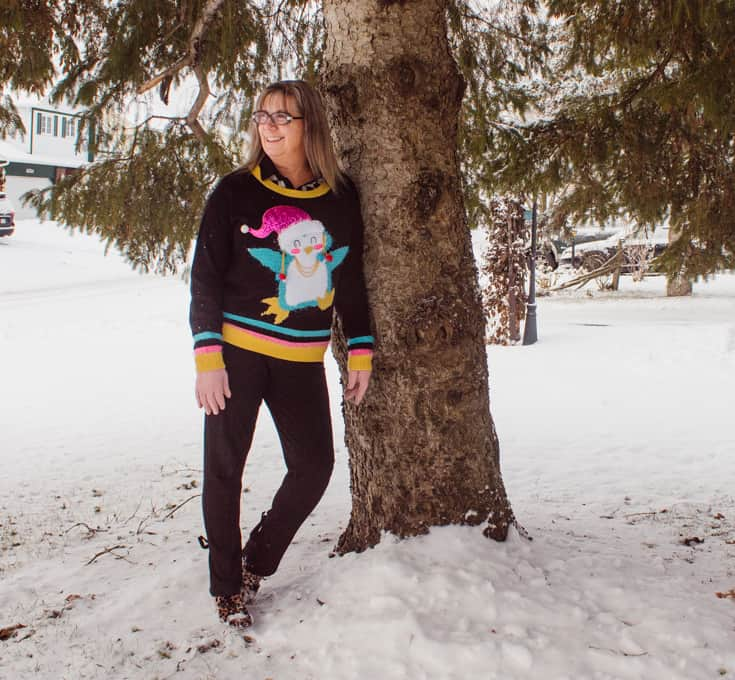 leaning on a tree with a fun sweater on