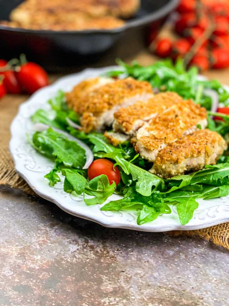 cheesy chicken cutlets on a white plate