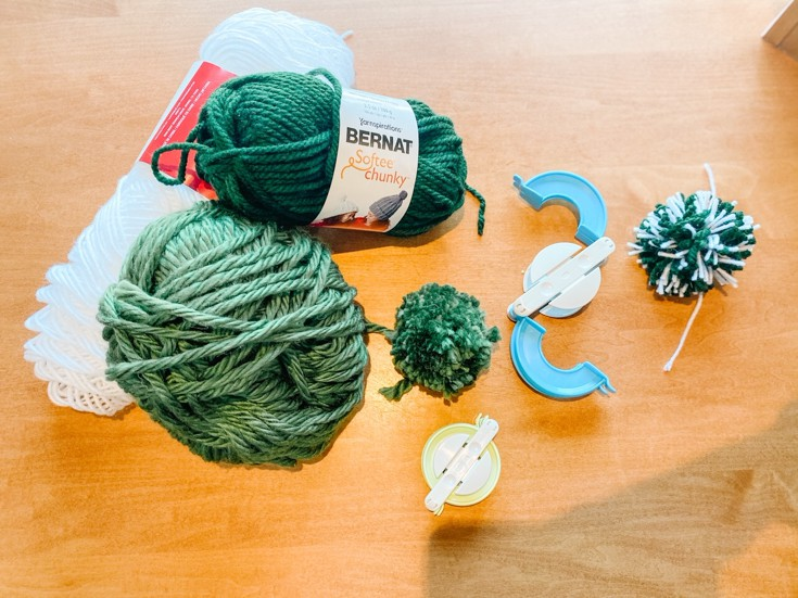 balls of yard and pom pom makers