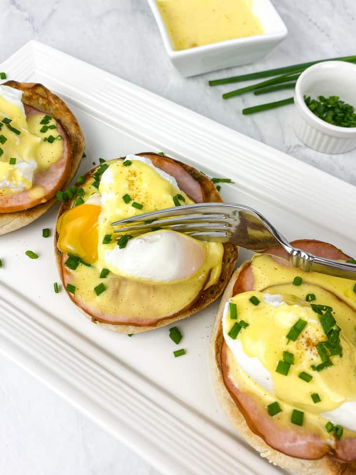 eggs benedict with hollandaise sauce on a plate for brunch