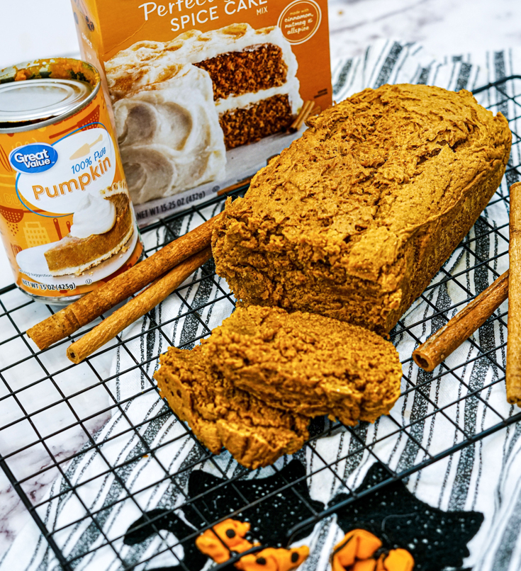 finished loaf of pumpkin bread with the ingredients needed.