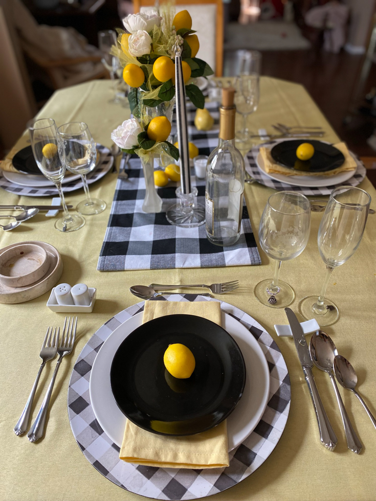 lemons onn a yellow tablecloth with black and white plates