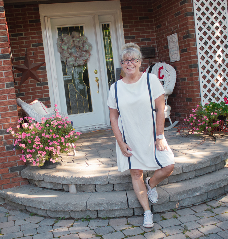 standing in a white linen dress